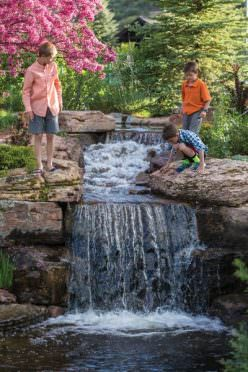 Kids play near a waterfall at Frost Creek