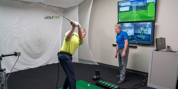 A man in the middle of a lesson at GOLFTEC.
