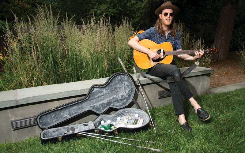 Wesley Schultz of the Lumineers poses with his guitar in the backyard of his Denver home.
