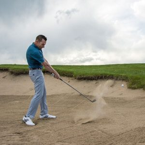 A golfer splashes a shot out of the bunker.