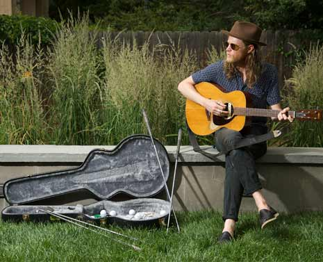 Wesley Shultz of the Lumineers plays the guitar on a stoop