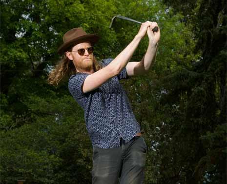 Wesley Schultz of The Lumineers swings a golf club