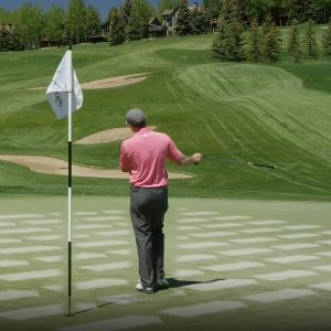A golfer checks out the contours of the green