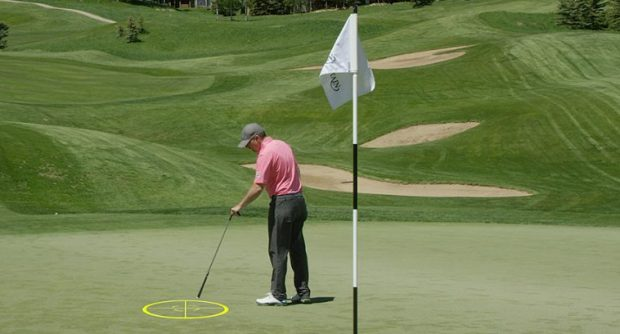 A golfer picks out a landing zone for his approach shot on the green.