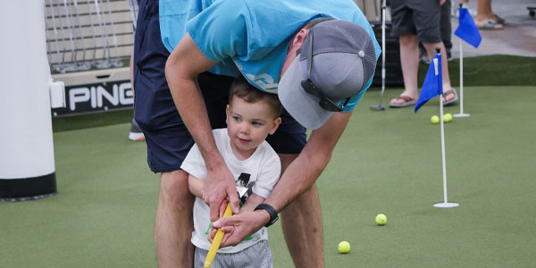 A child putts with his father at PGA TOUR Superstore