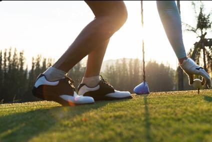 A golfer placing a ball on a tee.