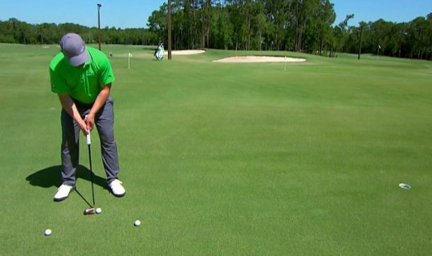 A golfer practices his putting stroke.