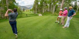 A golfer tees off in front of his buddies