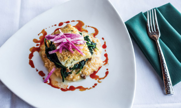 Blackstone's almond-crusted halibut crowns a layer of sautéed spinach atop a creamy shrimp-and-chorizo risotto.