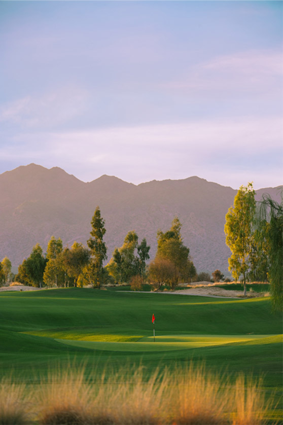 The mountains rise behind one of the holes at Ak-Chin Southern Dunes Golf Club