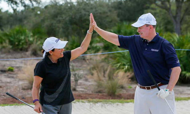 Elena King high fives one of her students (Photo courtesy ExperienceGolf)