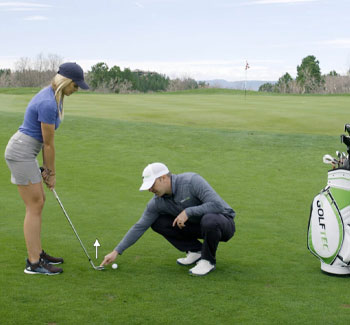 GOLFTEC instructor helps teach how to chip onto the green