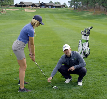 A GOLFTEC instructor teaches a student to hit from the rough