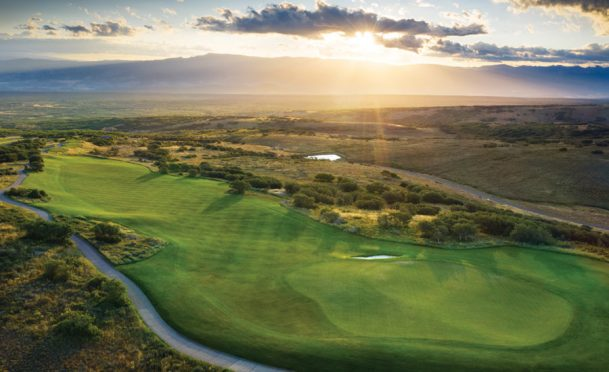 A NEW DAY DAWNS: Rising over the West Elk Mountains, the morning sun butters the 12th green at Cornerstone.